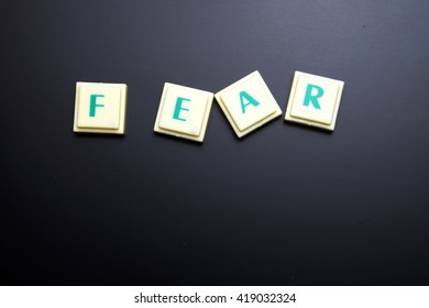 Fear concept. The words spelled by letters on black board background. Space for texts.