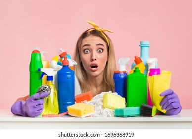 Fear of coronavirus. Shocked housewife hugs cleaning supplies, free space