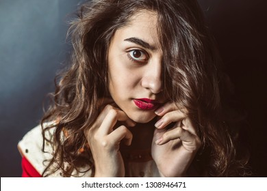 Fear and danger on the face of an Arab girl with beautiful eyes. A muslim woman looking thoughtfully at the camera. Indian female on black background.