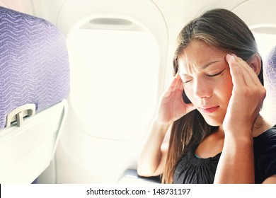 Fear of flying woman in plane airsick with stress headache and motion sickness or airsickness. Person in airplane with aerophobia scared of flying being afraid while sitting in airplane seat.