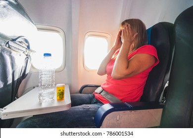 Fear of flying woman in plane airsick with stress headache and motion sickness or airsickness. Focus on bottle and tablets.