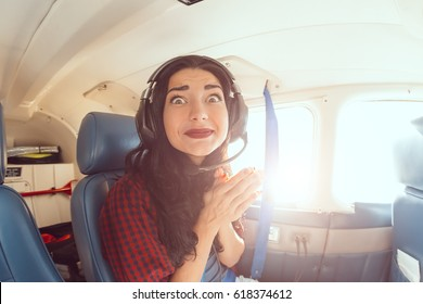 Fear of flying woman in plane . Person in airplane with aerophobia scared of flying being afraid while sitting in airplane seat. Funny girl portrain on fish eye lense
