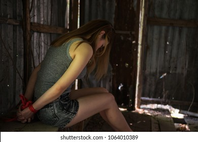 Fear Victim woman hands tied by red rope  in abandon house. Hostage concept or female kidnapped from robber. Sexual abuse in dirty stair with copy space for text.