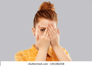 fear, vision and shame concept - scared, shy or embarrassed red haired teenage girl closing one eye by hand and looking through fingers over grey background
