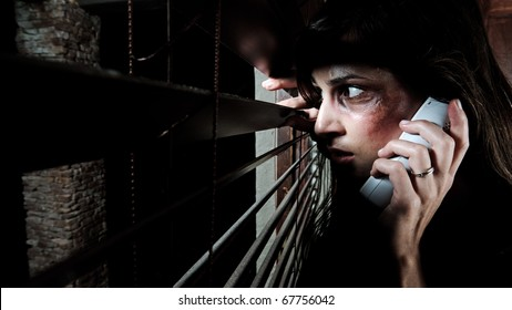 Fearful battered woman peeking through the blinds to see if her husband is home while calling for help