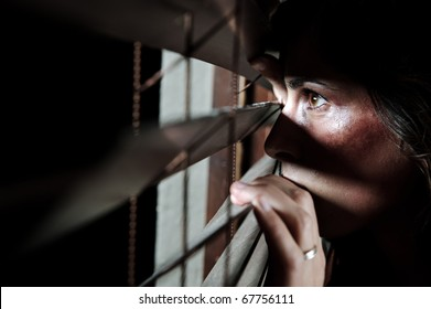 Fearful battered woman peeking through the blinds to see if her husband is home