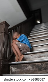 Fearful child sitting on a wooden staircase