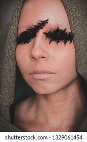 Fearful close-up portrait of young woman without eyes with cape on her head. Creepy halloween character