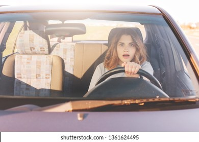 Fearful driving woman, learns to drive automobile, attractive female sits at wheel alone for first time, tries to avoid car accident, has frightened facial experessions, wants to stop vehicle.