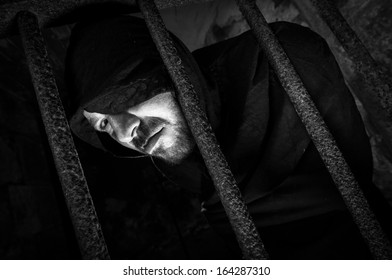 fearful hooded man in jail