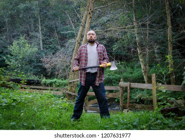 Fearful lumberjack standing with an axe - stunning background with a river and forest