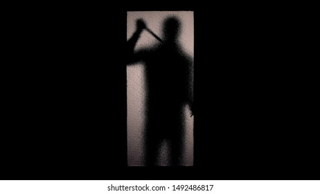 Fearful silhouette of man with knife standing near glass door maniac breaking in