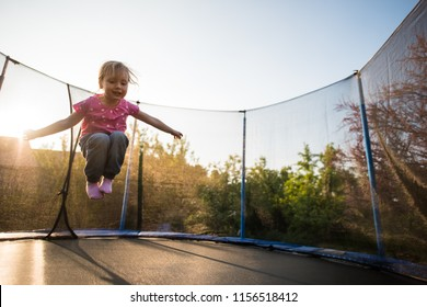 Fearless child jumping high on the trampoline bed
