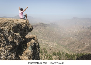 Fearless hiker sitting on top of rock edge enjoying mountain landscape in Gran Canaria. Confident man celebrating nature beauty with arms up. Courage, dare, no fear, victory, winner concepts