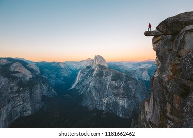 A fearless hiker is standing on an overhanging rock enjoying the view towards famous Half Dome at Glacier Point overlook in beautiful evening twilight, Yosemite National Park, California, USA