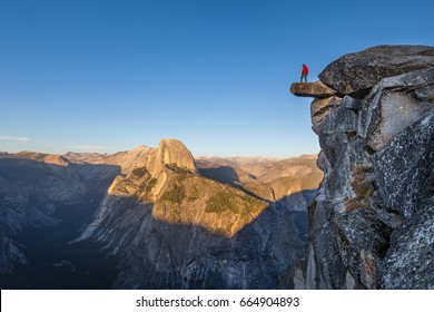 A fearless hiker is standing on an overhanging rock enjoying the view towards famous Half Dome at Glacier Point overlook in beautiful evening sunset twilight, Yosemite National Park, California, USA