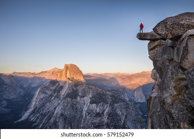 A fearless male hiker is standing on an overhanging rock at Glacier Point enjoying the view over Half Dome at sunset in beautiful twilight at sunset in summer, Yosemite National Park, California