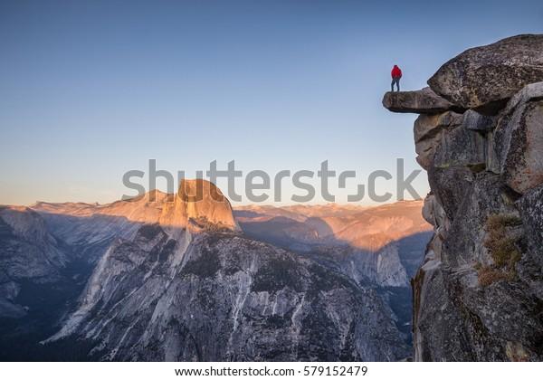 Un randonneur courageux se tient sur un rocher surplombant Glacier Point et profite de la vue sur la Demi-Dôme au coucher du soleil, au coucher du soleil, au coucher du soleil, dans le parc national Yosemite, en Californie