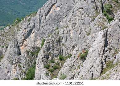 Fearless mountain climber with equipment hanging over dangerous ravine performing stunts on slack line. Daredevil travelers enjoying difficult climbing routes