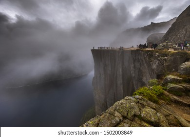 Fearless and risky people stand on the edge of the abyss of the famous giant cliff Pulpit Rock in the clouds with a crazy storm wind and rain over the fjord in Norway.