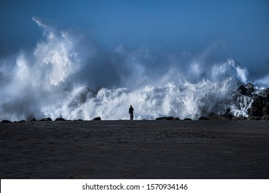 Fearless woman standing against the big waves. Stay strong in tough days.