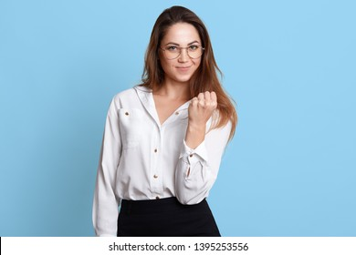 Fearsome elegant bossy manager standing firmly, holding clenched hand, showing fist, looking directly at camera. Long haired confident model posing in white formal blouse and black skirt, specs.