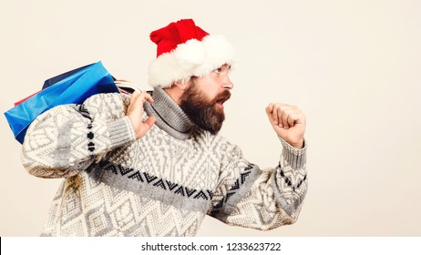 Feast of Christmas. Funny man with a big beard in a sweater is in a hurry to go shopping, runs for New Year discounts or for Christmas sales.