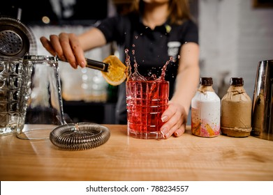 feat blonde barmaid in black shirt adding to the cocktail glass slice of lemon using tongs at the bar counter