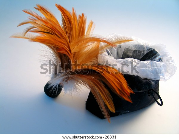 A feather brush leaning up against a bag of body powder
