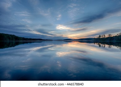 Feather clouds on a deep blue sunset sky reflected in still water of Naismeri bay in Ladoga lake, Republic of Karelia, north-west of Russia