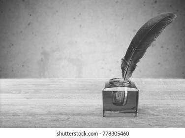 Feather with inkwell on wooden desk.