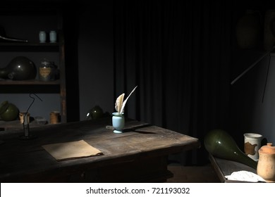 Feather pen on wooden table in dark room