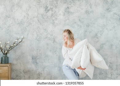 Feather pillow comfort. Young satisfied blonde woman holding pile of pillows. Copy space on grey background.