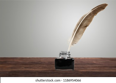 Feather quill pen and glass inkwell isolated