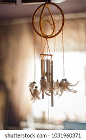 Feathered dreamcatcher on ceiling, hanging from a lamp, with wind chimes attached