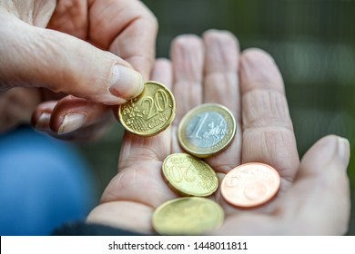 Feature image poverty: Poor and scruffy woman is holding Euro and Cent coins in her hand - close-up with selective focus with very little depth of field