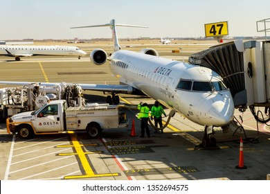 FEB 14, 2019 JFK NEW YORK, USA: Small jet airplane with attached at airport gate terminal during DELTA JFK International Airport