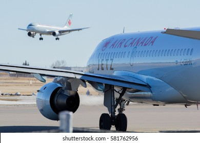 FEB 17, 2016 - CALGARY, AB. An Air Canada charter jet taxis to runway 35L at Calgary International Airport while another Air Canada jet lands.