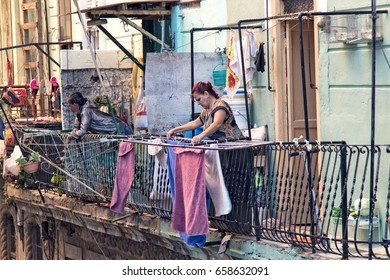 FEB. 18, 2017- HAVANA, CUBA - A Cuban woman hangs laundry on the wrought iron balcony railing of her apartment in Havana, Cuba.