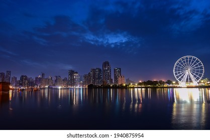 Feb 19, 2021,Sharjah, United arab emirates.Panoramic view of the sky scrapers of  Sharjah along with the amusements rides in the Montazah park captured from the Majaaz park , Sharjah, UAE.