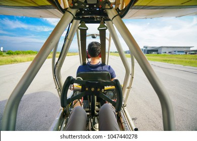 FEB 2018 - BANGKOK, THAILAND: The passenger sits at the back of the pilot on Ultralight Quicksilver GT500 aircraft ready to take off from the runway at Best Ocean airport.
