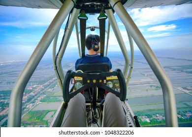 FEB 2018 - BANGKOK, THAILAND: The pilot has controlled the Ultralight aircraft, Quicksilver GT500 flying on the vivid blue sky over Samut Sakhon and Bangkok in Thailand.