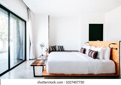 FEB 23, 2015 Kanchanaburi, Thailand : White contemporary hotel style bedroom with white linen high ceilling and vintage floor fan