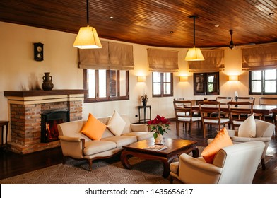 FEB 25, 2014 Dalat, Vietnam - Vintage colonial living room hard wood floor and ceiling with sofa couch, armchairs. Furnished with old wood coffee table, colourful pillows, retro clock and fireplace