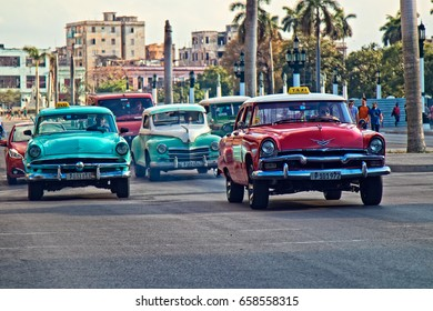 FEB. 25, 2017- HAVANA, CUBA - A group of vintage cars drive down the street in Havana, Cuba.