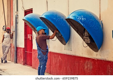 FEB. 25, 2017 - HAVANA, CUBA - A man uses a public telephone that is encased in a blue bubble, while another man speaks on an intercom phone.