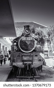 FEB 26, 2014 Dalat, Vietnam - Old Dalat railway station - Vietnam with vary old grungy locomotive steam train engine at platform with tourists. black and white image