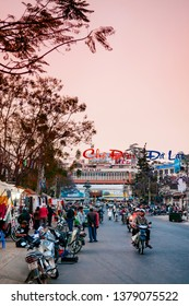 FEB 26, 2014 Dalat, Vietnam - Vary busy evening with local motorcycle traffic at night market in Dalat city. Building with Alphabet neon light at Da Lat city center