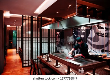 FEB 8, 2013 Phuket, Thailand - Asian chef grilling lobster on  flat griddle pan in open kitchen Japanese Teppanyaki restaurant