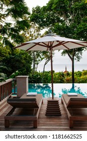 FEB 9, 2013 Phuket, THAILAND - Vacation Relaxation resort daybed under umbrella by the infinity pool in lush green tropical garden